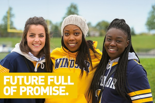 Students smiling behind banner reading: Future full of promise