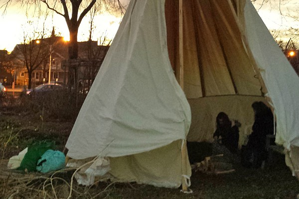 students in teepee in the Campus Community Garden