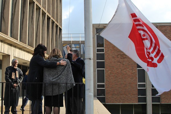 UWindsor and United Way officials raise the charity's flag outside Chrysler Hall Tower to kick off last year's fundraising effort.