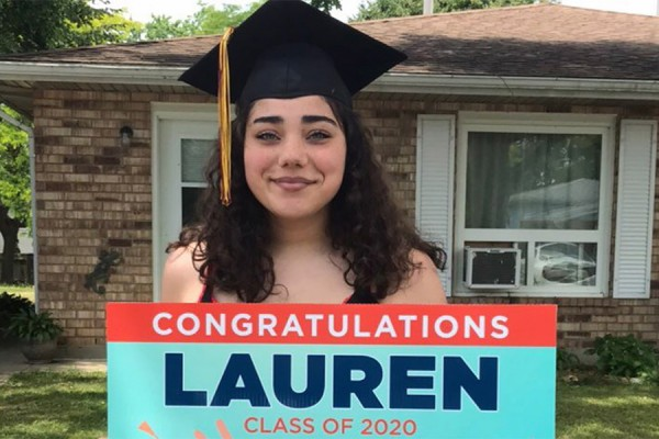 "Young woman wearing mortarboard and holding sign that reads ""Congraulations Lauren"""