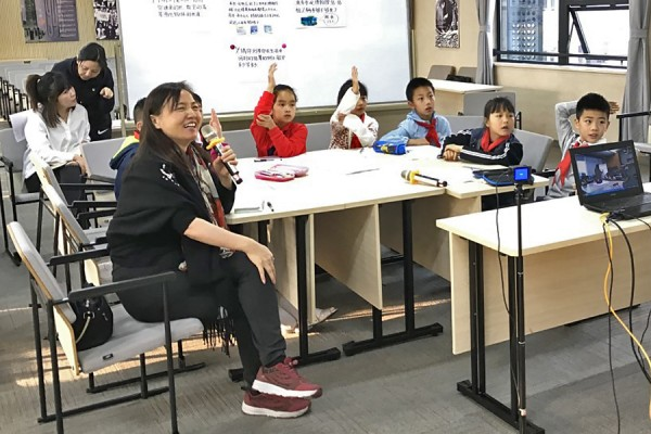 Education professor Shijing Xu sits in a Chongqing, China, classroom in 2019, using Skype to meet with a sister school in Windsor.