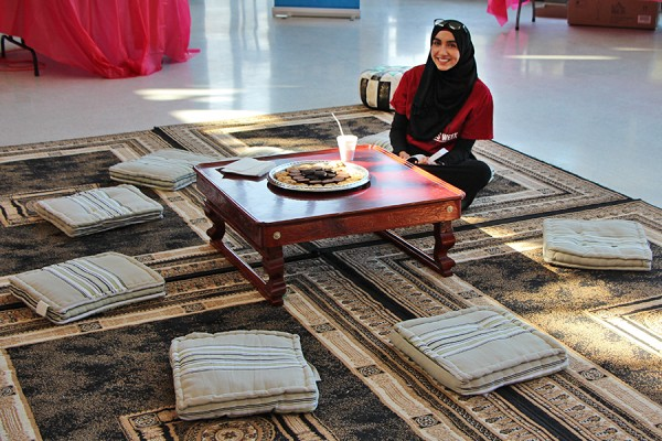 Biology major Yosra Elsayed volunteers to speak with guests on a prayer mat in the student centre Monday.