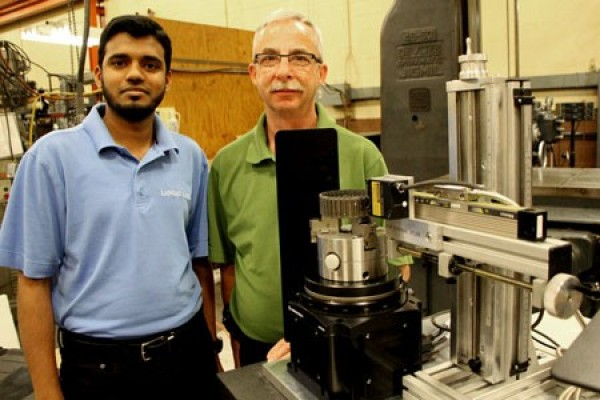 Shanawaz Ali Mohammad and Ken Bishop stand with the laser-based custom measuring machine