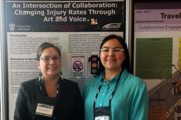 UWindsor PhD student Naomi G. Williams (l.) and research partner Anika Altiman (r.) pose with their poster tailored to incorporate Indigenous languages and art in a campaign to reduce the risk of vehicular injury among Indigenous people in Walpole Island