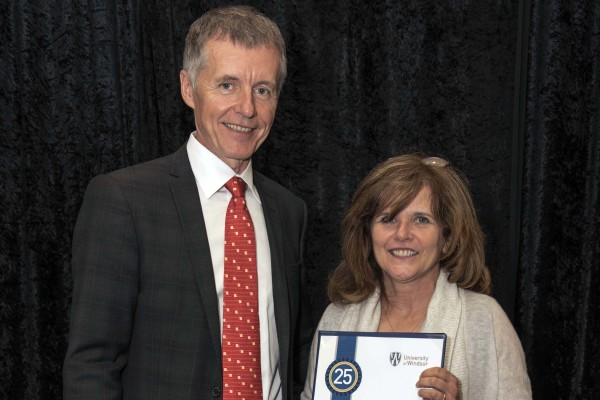 Jackie Imeson, who reached 25 years of service in 2015, accepted congratulations from UWindsor president Alan Wildeman during a luncheon on June 12.