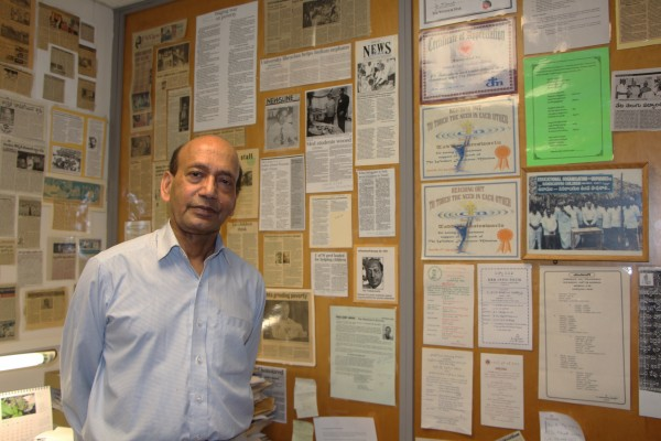 Retired UWindsor librarian and sessional instructor in economics Dr. Tad Venkateswarlu poses with numerous news clippings about his Tenali School Project.