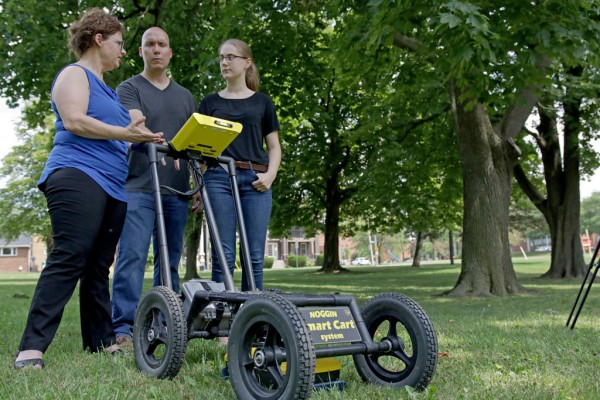Earth and Environmental Sciences Professor Maria Cioppa, History professor Guillaume Teasdale and high school student Grace Dycha examine the readings on the Noggin ground penetrating radar.